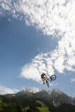 El freestyler joven salta con su bmx arriba en el aire Fotos de archivo