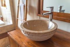 El fregadero hecho a mano del lavado de la mano hizo de piedra en un cuarto de baño del hotel de lujo imagen de archivo