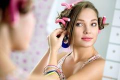 El frente de la chica joven el espejo pone el pendiente Fotos de archivo