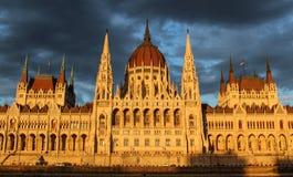 El frente húngaro del edificio del parlamento en el banco del río Danubio expuesto a los rayos del sol del sistema del sol con el fotos de archivo