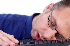 El friki nerdy masculino se cae dormido en el teclado Fotografía de archivo