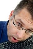 El friki nerdy masculino se cae dormido en el teclado Imagenes de archivo