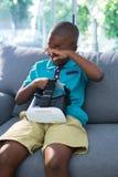 El frotamiento cansado del muchacho observa mientras que se sienta con las auriculares de VR en casa imagen de archivo