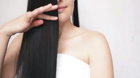 El frotar ligeramente de la chica joven entrega el pelo largo que demuestra su suavidad y Silkyness Se?ora bonita Cares Over Hair metrajes
