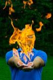 El fuego al aire libre se enciende para arriba en las manos de Imágenes de archivo libres de regalías
