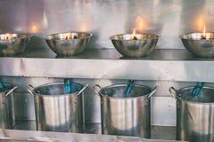 El fuego de la lámpara de aceite para encendió la vela en Fotografía de archivo