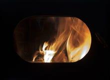 El fuego en el hogar, en la ventana oval del horno Fotos de archivo