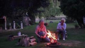 El fuego en la cesta de fuego es encendido por el hombre, la mujer mira a su marido metrajes