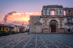 El Fuego Sunset and a beautiful Ruin in Antigua. In foreground the ruin of the Church & School of the Society of Jesus, Antigua, Guatemala, and in the background royalty free stock photo