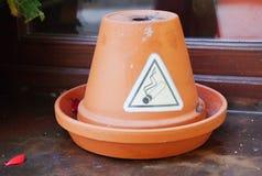 El fumar permitido firma adentro la forma del triángulo en el pote de cerámica en el travesaño de la ventana foto de archivo libre de regalías