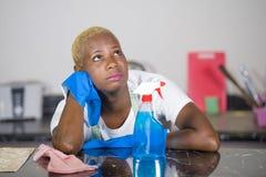 El funcionamiento afroamericano triste y deprimido hermoso joven de la mujer negra subrayado y cansó en casa la limpieza trabajad foto de archivo