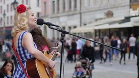 El funcionamiento de la calle, muchacha con una flor en su pelo canta y toca la guitarra en el micrófono