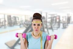 El funcionamiento de la mujer está con los pesos en el gimnasio Fotos de archivo libres de regalías