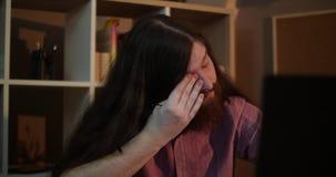 El funcionamiento de vidrios del hombre que llevaba barbudo joven con el ordenador portátil en oficina oscura tarde en la noche,  almacen de metraje de vídeo