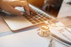 El funcionamiento del doctor en el ordenador portátil, clipbo de la prescripción de la escritura fotos de archivo