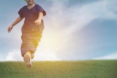 El funcionamiento del niño y el jugar tienen la diversión y alegría en el campo de hierba foto de archivo