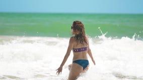 El funcionamiento feliz joven de la mujer en el mar con la porción de salpica y salto sobre la onda de fractura almacen de metraje de vídeo