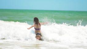 El funcionamiento feliz joven de la mujer en el mar con la porci?n de salpica y salto sobre la onda de fractura almacen de video