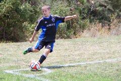 El futbolista del fútbol de la juventud golpea la bola con el pie Fotos de archivo libres de regalías