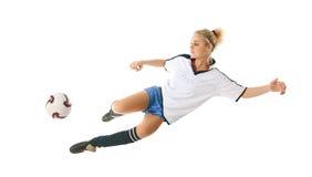 El futbolista femenino en saltar-golpea la bola con el pie Foto de archivo