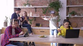 El futuro ahora está, la mujer joven con los vidrios de realidad virtual juega a juegos mientras que los colegas rato comen y de  metrajes