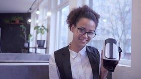 El futuro ahora está, muchacha adolescente afroamericana feliz en gafas pone en casco de la realidad virtual en cámara