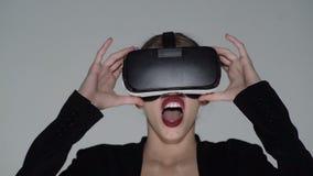El futuro ahora est? Tacto hermoso de la mujer algo usando los vidrios modernos de la realidad virtual El llevar atractivo de la  almacen de video
