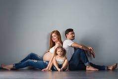 El futuro joven parents un hombre y a una mujer embarazada pelirroja con fotografía de archivo