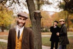 El gángster en un traje y un casquillo en el parque fuma Concepto retro Fotografía de archivo libre de regalías