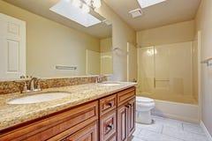 El gabinete de cuarto de baño con dos fregaderos y el granito rematan Fotos de archivo