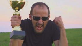 El ganador con un casquillo en sus manos aumenta sus manos, disfruta de éxito almacen de video
