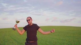 El ganador con una recompensa en sus manos aumenta sus manos, disfruta de éxito Él salta y baila almacen de metraje de vídeo