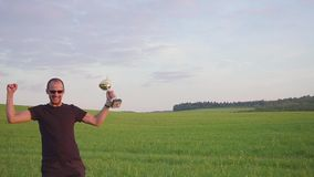El ganador con una recompensa en sus manos aumenta sus manos, disfruta de éxito Él salta y baila metrajes