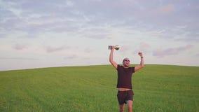 El ganador con una recompensa en sus manos aumenta sus manos, disfruta de éxito Él salta y baila almacen de video
