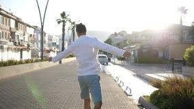 El ganador divertido hace caras graciosamente, salta y gira un camino de ciudad en día soleado del verano almacen de metraje de vídeo