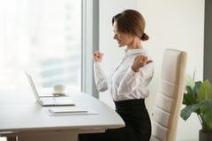 El ganador feliz de la empresaria siente excitado leyendo buenas noticias en el em fotos de archivo