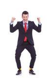 El ganar de mirada divertido del hombre de negocios Foto de archivo