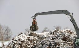El gancho agarrador hidráulico limpia y los tampens la ruina del metal El excavador levanta y lanza la carga con una pata neumáti foto de archivo libre de regalías