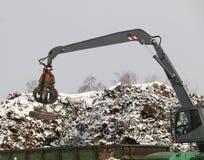 El gancho agarrador hidráulico limpia y los tampens la ruina del metal El excavador levanta y lanza la carga con una pata neumáti imagen de archivo libre de regalías