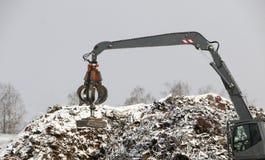 El gancho agarrador hidráulico limpia y los tampens la ruina del metal El excavador levanta y lanza la carga con una pata neumáti fotos de archivo libres de regalías