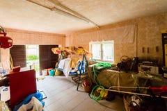 El garaje del garagThe con el acceso a la yarda se equipa de un cuarto de caldera y artículos descompuestos del hogar y un oscila fotografía de archivo libre de regalías