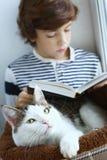El gato pone en cama del animal doméstico con el libro de lectura del muchacho Imágenes de archivo libres de regalías
