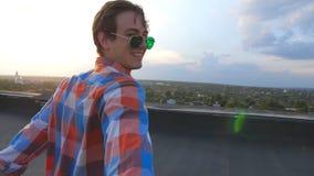 El gay hermoso lleva a cabo la mano de su novio y corre para afilar del tejado para admirar la visión Sígame que el tiro del homb almacen de metraje de vídeo
