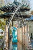 El geisha bastante joven en agua cae en el vestido azul que coloca la fuente cercana Foto de archivo libre de regalías