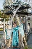 El geisha bastante joven en agua cae en el vestido azul que coloca la fuente cercana Imágenes de archivo libres de regalías