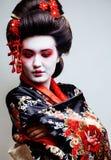 El geisha bonito joven en kimono con Sakura y la decoración roja diseñan en el fondo blanco Fotos de archivo libres de regalías