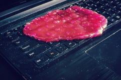 El gel de la limpieza del teclado está poniendo en el cuaderno Foto de archivo libre de regalías