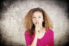 El gesticular de la niña guarda el secreto, tranquilidad, silencio Imagen de archivo libre de regalías