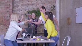 El gesto de la victoria, equipo amistoso del negocio dobló las manos y levanta su para arriba en oficina almacen de video