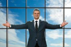 El gesto que da la bienvenida del hombre de negocios adulto Fotografía de archivo